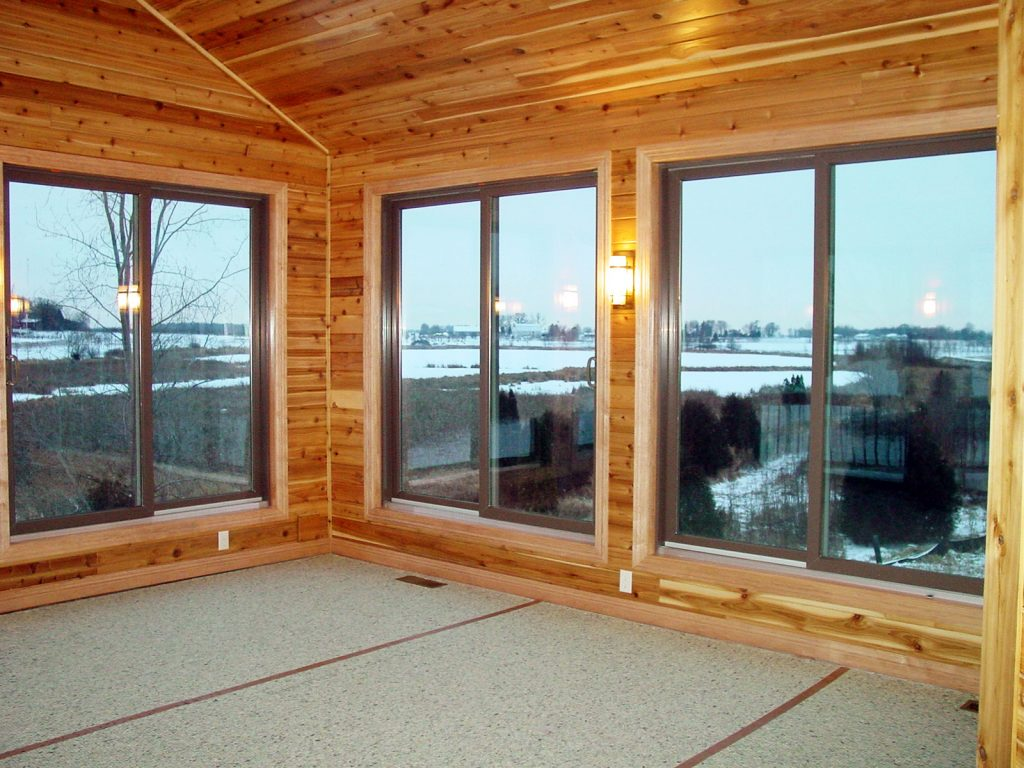 Enclosed porch with wood paneling and large windows