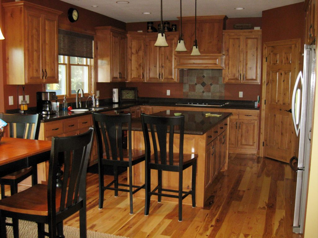 New kitchen with wood cabinets and dark stone countertops