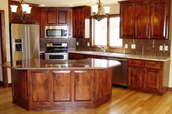 New kitchen with wood cabinets, hardwood floors and stone countertops