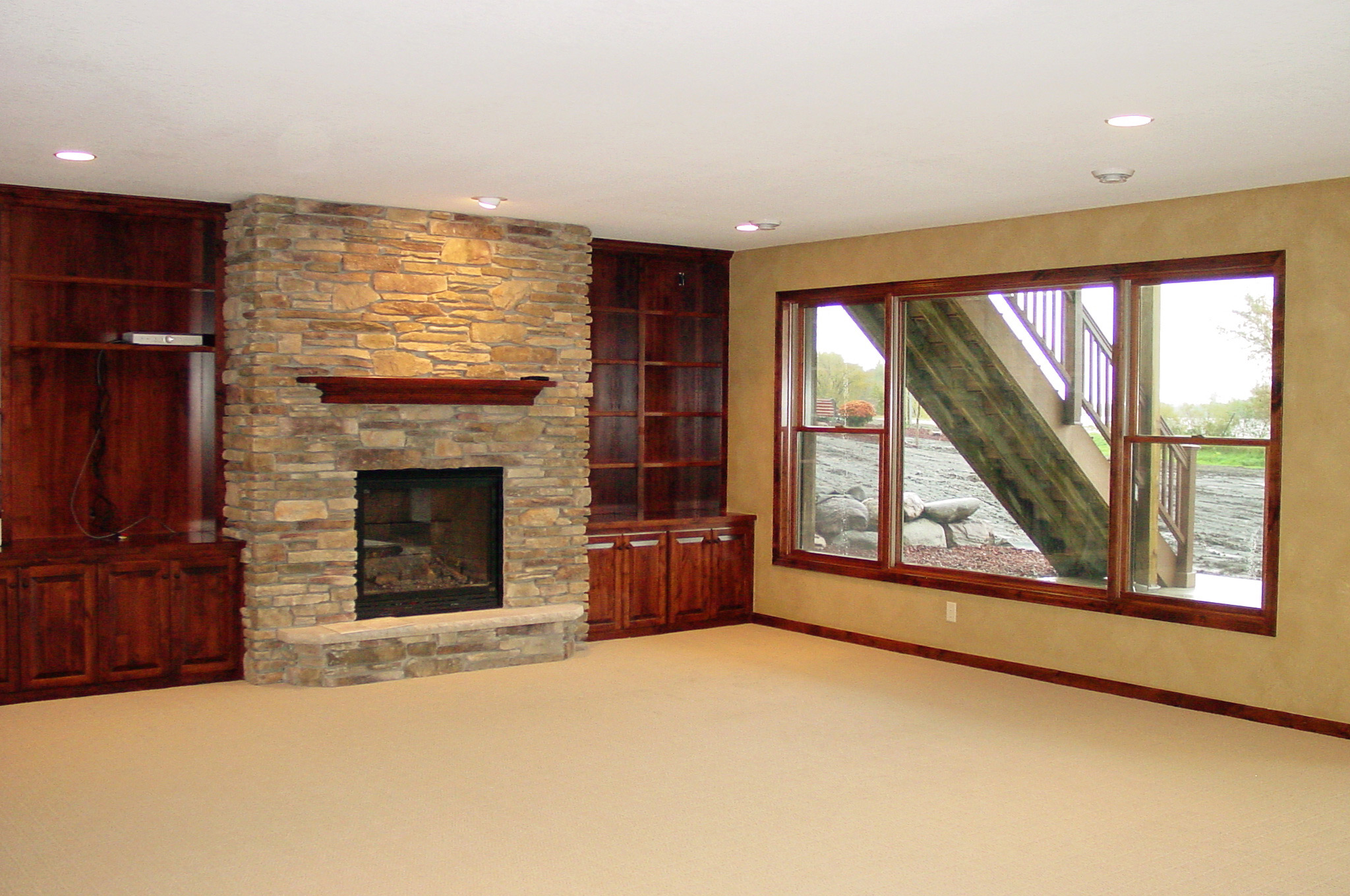 Lower level family room with wood built-ins and stone fireplace