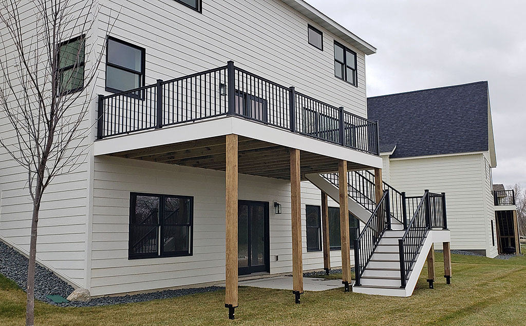TimberTech composite decking with helical posts, metal balusters, stairway with landing to ground elevation