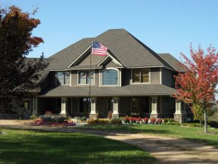 Olive house with front porch and American flag