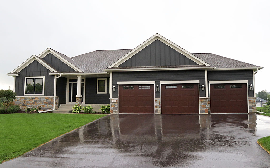 Rambler with three-stall garage, stone wainscoat, board and batten siding and wide accent trim