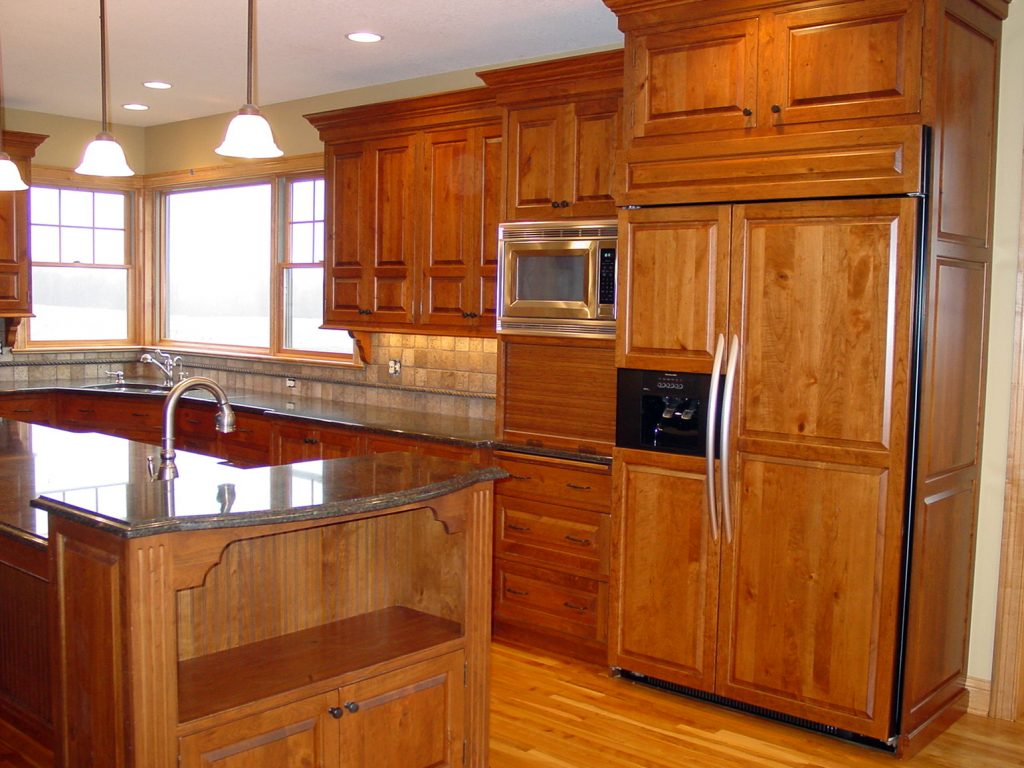 New kitchen with wood cabinets, stone countertops and custom panel fridge