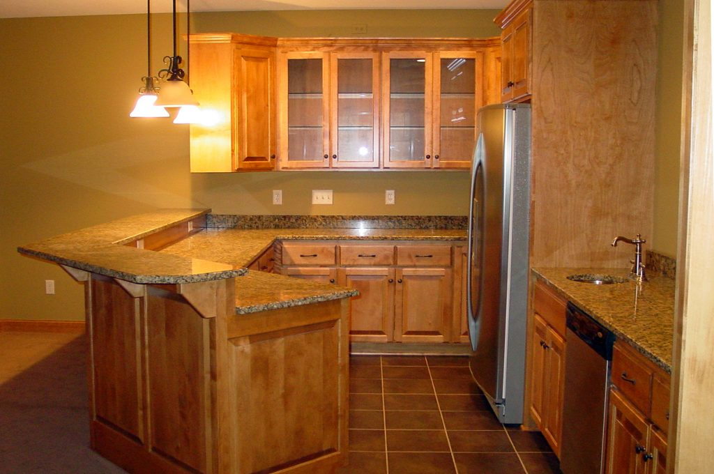 New kitchen with wood cabinets, stone countertops and tile floor