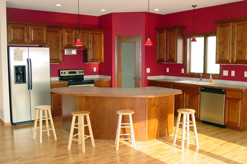 Red kitchen with wood cabinets and curved island