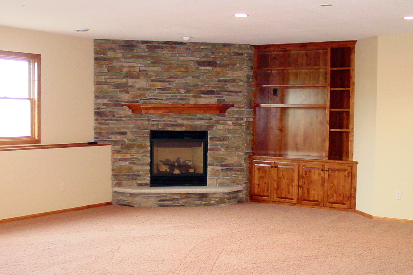 Lower level family room with stone fireplace and wood built-ins