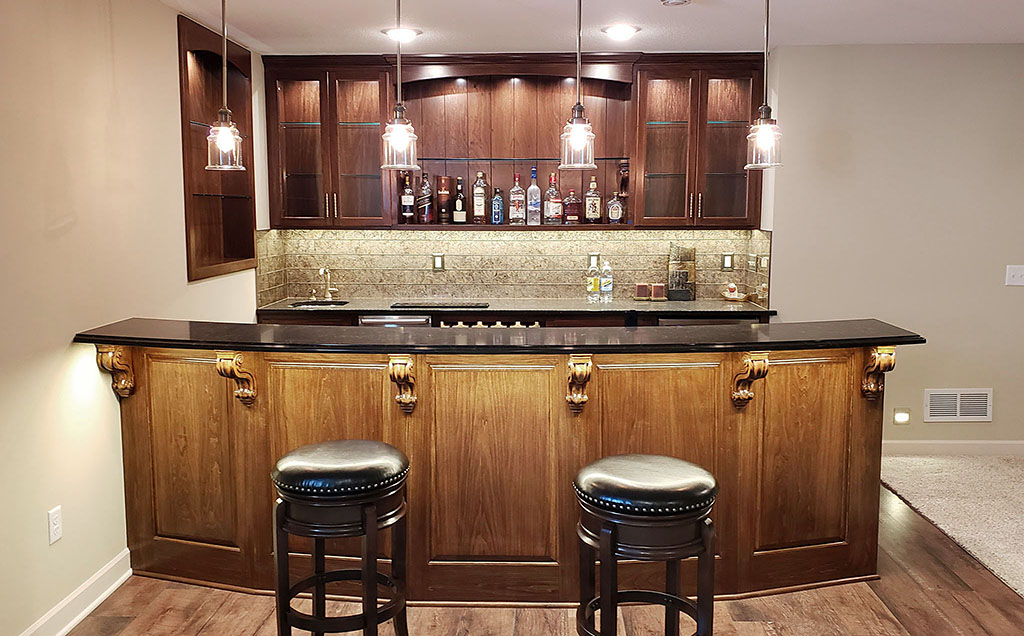 Basement bar area with curved bartop, stone backsplash, custom built-in cabinets with glass doors & shelves