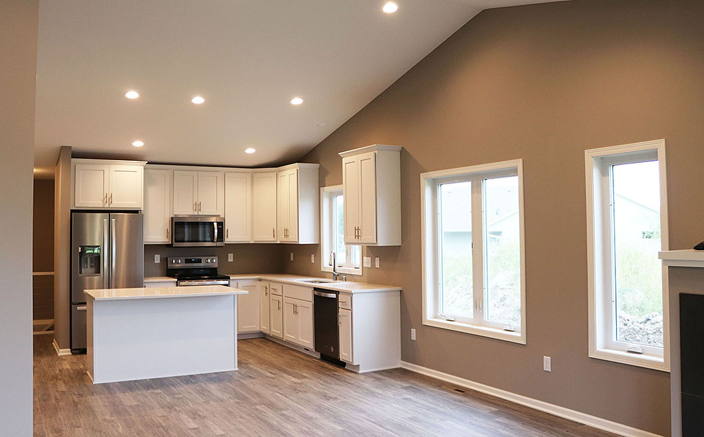 Twin home living and kitchen with vaulted ceiling