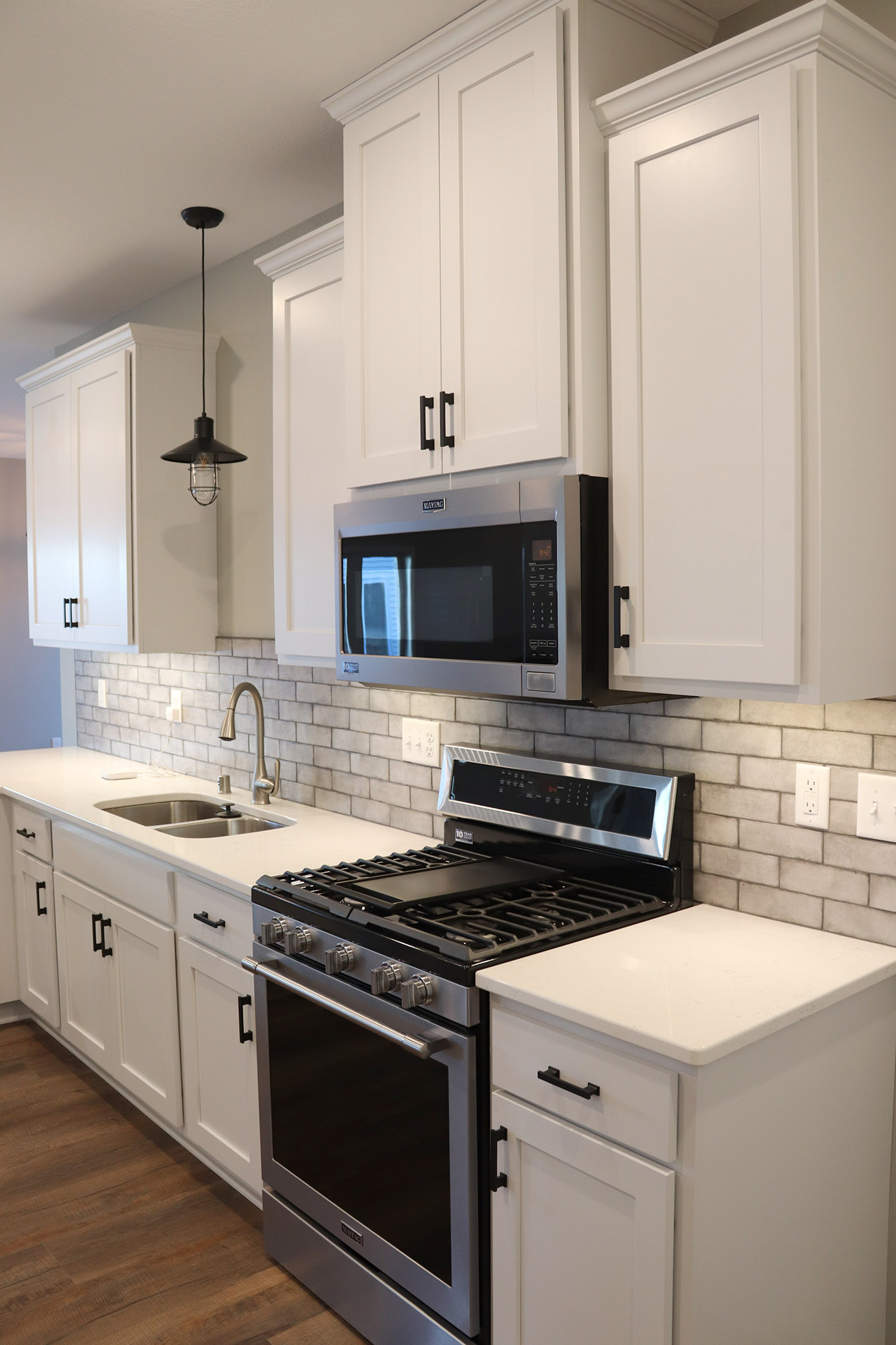 White kitchen cabinets with white granite countertops, undermount sink, ceramic tile backsplash and stainless steel appliances