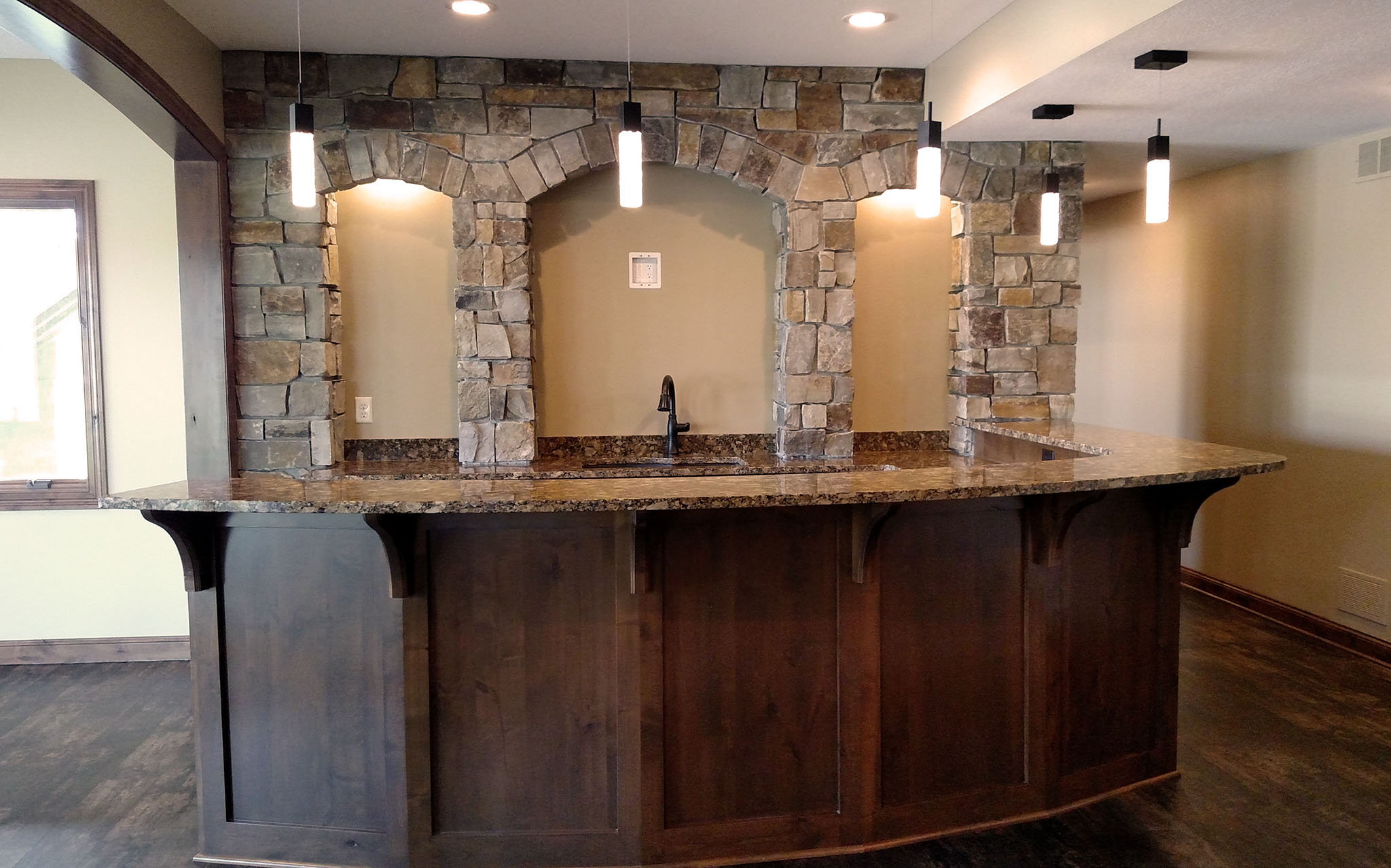 Basement bar area with stone arch accent wall and curved granite bartop