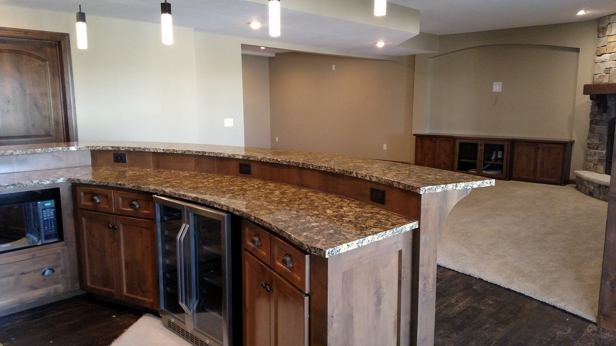 Basement bar area with custom cabinets, curved two-level granite countertops and spacious family room in background