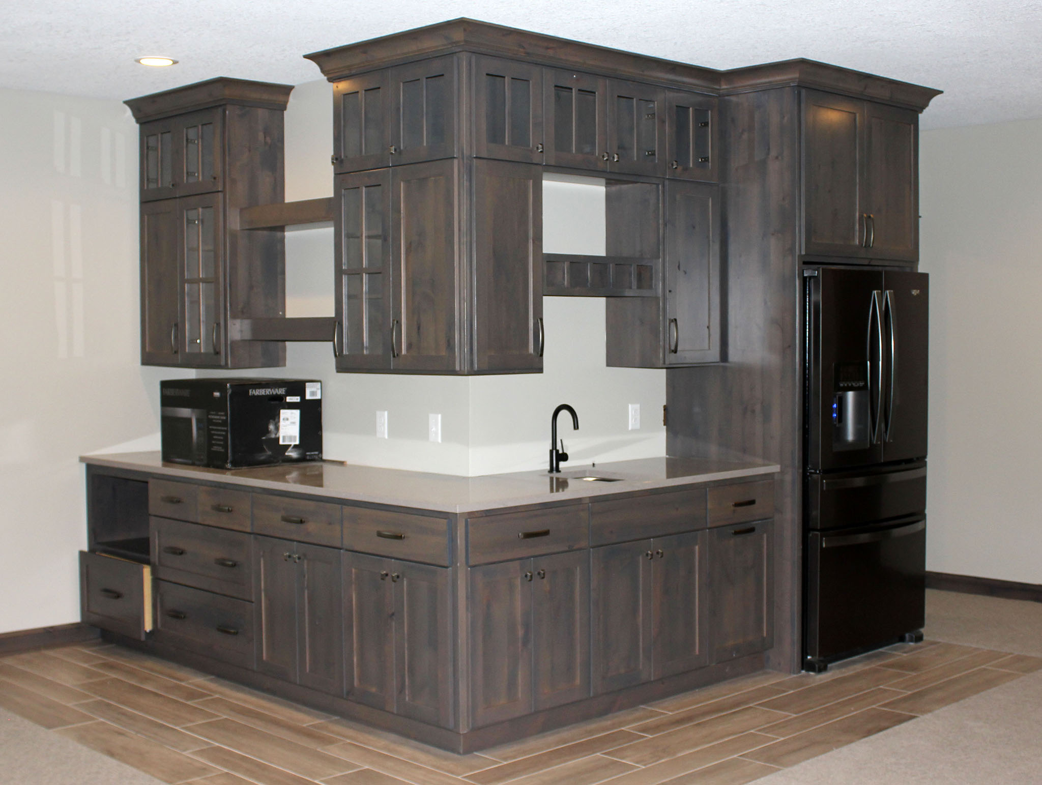Two-sided basement bar oasis with floor to ceiling custom cabinets, wine rack and glass cabinet doors