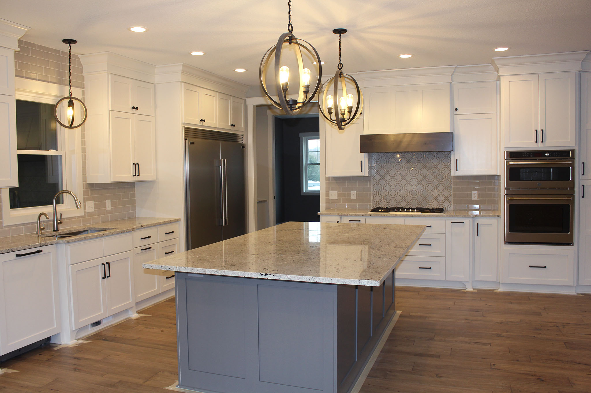 Spacious kitchen with floor to ceiling custom cabinets, granite countertops and ceramic tile backsplash