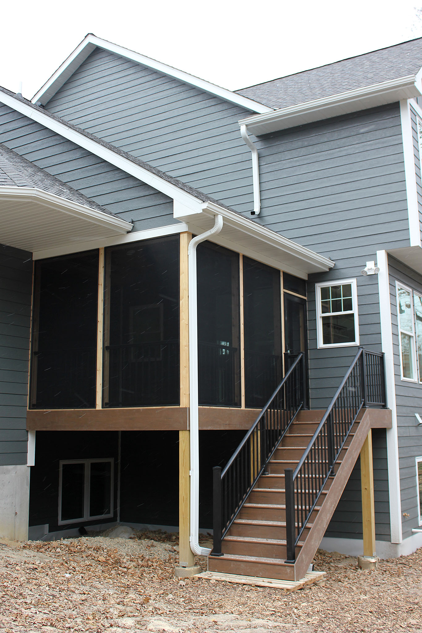 Screen porch with TimberTech composite decking with metal balusters and railing, stairway to ground elevation