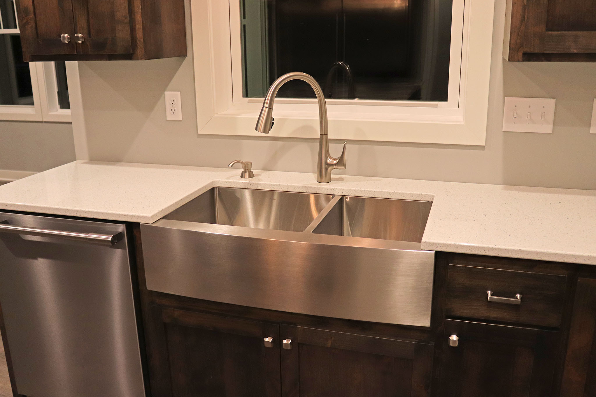 Closeup of kitchen stainless steel farm sink and quartz countertop