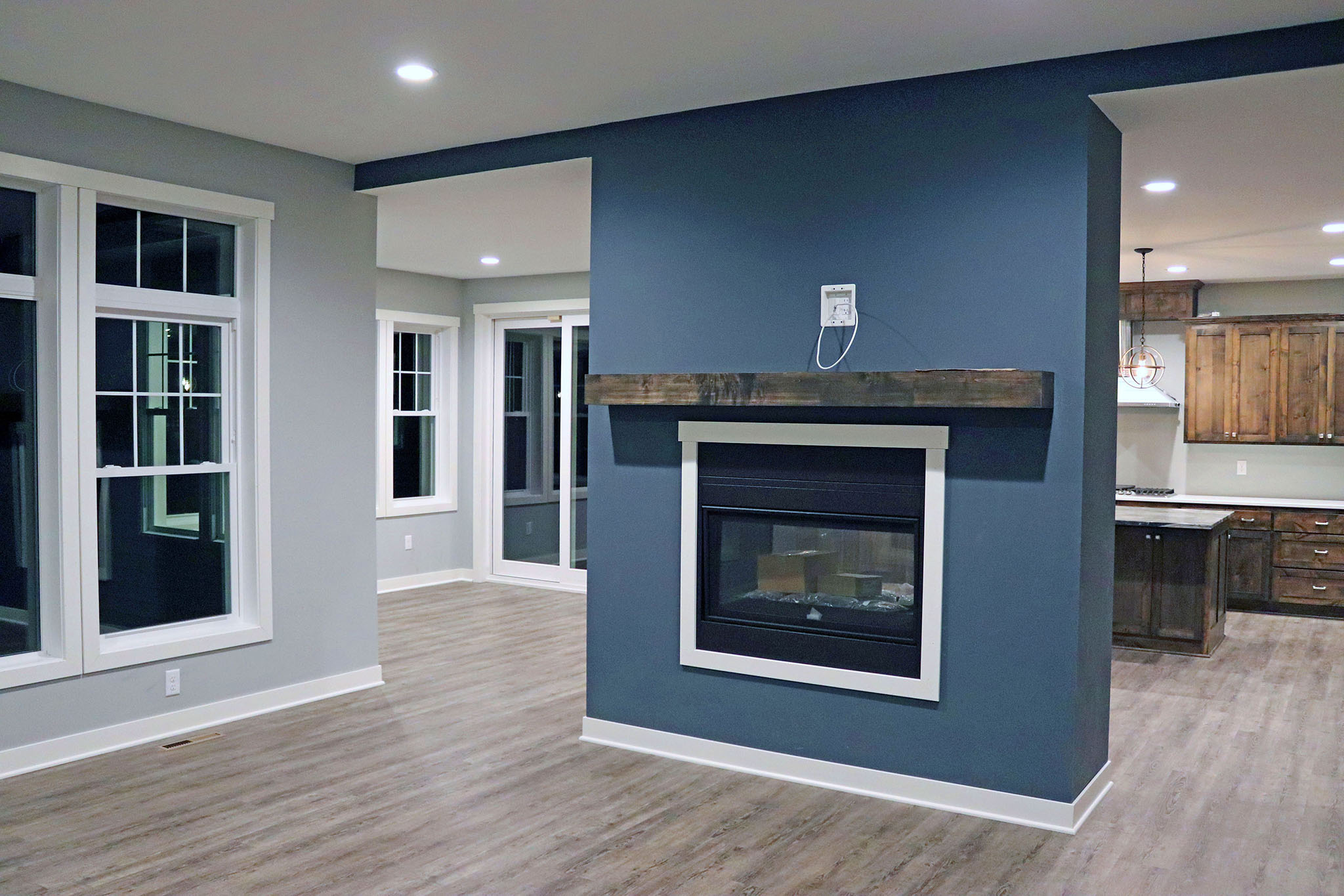 Double-sided fireplace with wood mantle