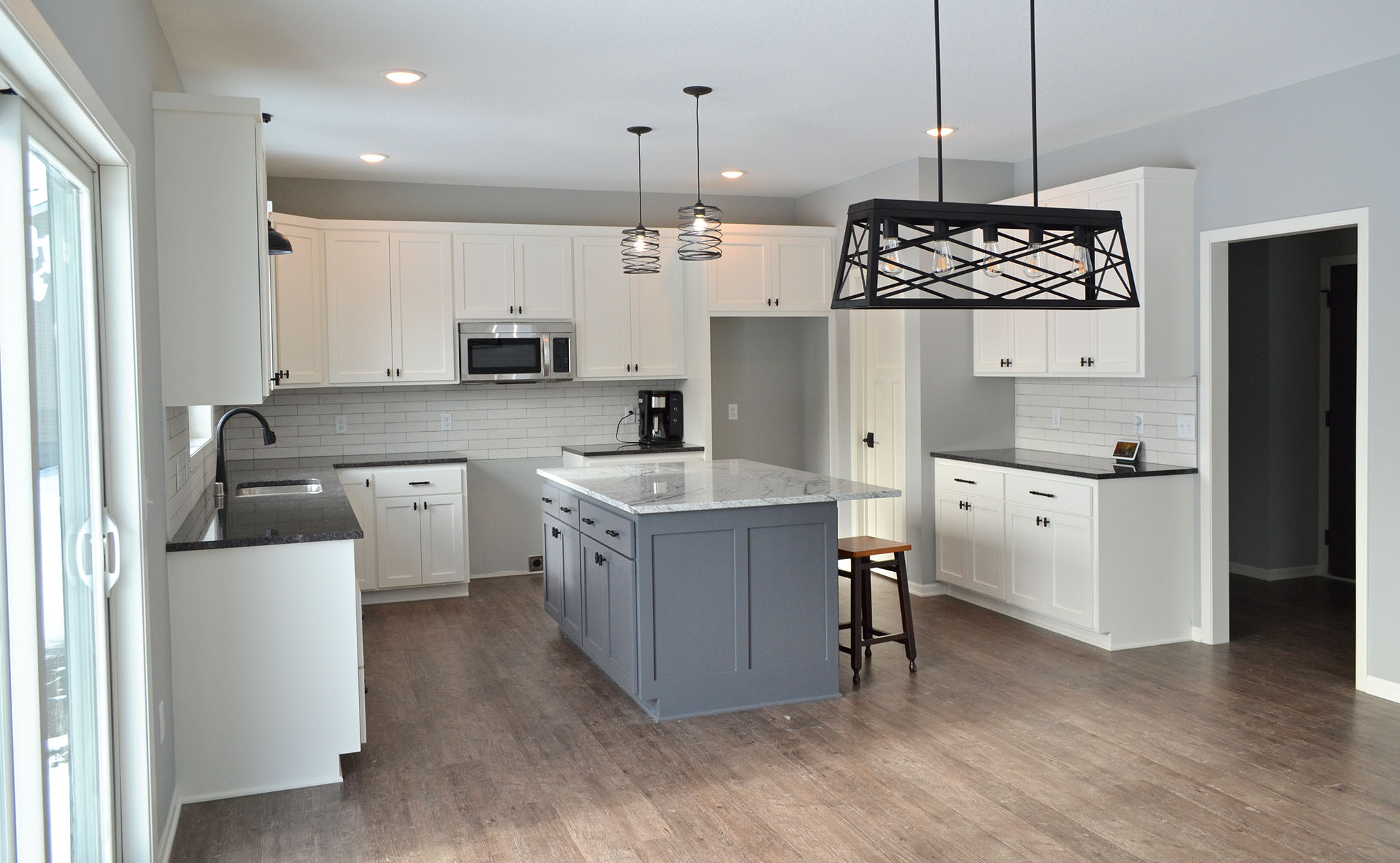 Large kitchen with white custom cabinets, gray island and granite countertops