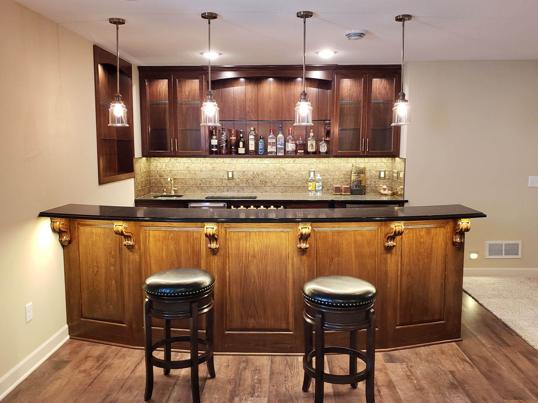 Basement bar area with curved bartop, stone backsplash, custom built-in cabinets with glass doors and shelves