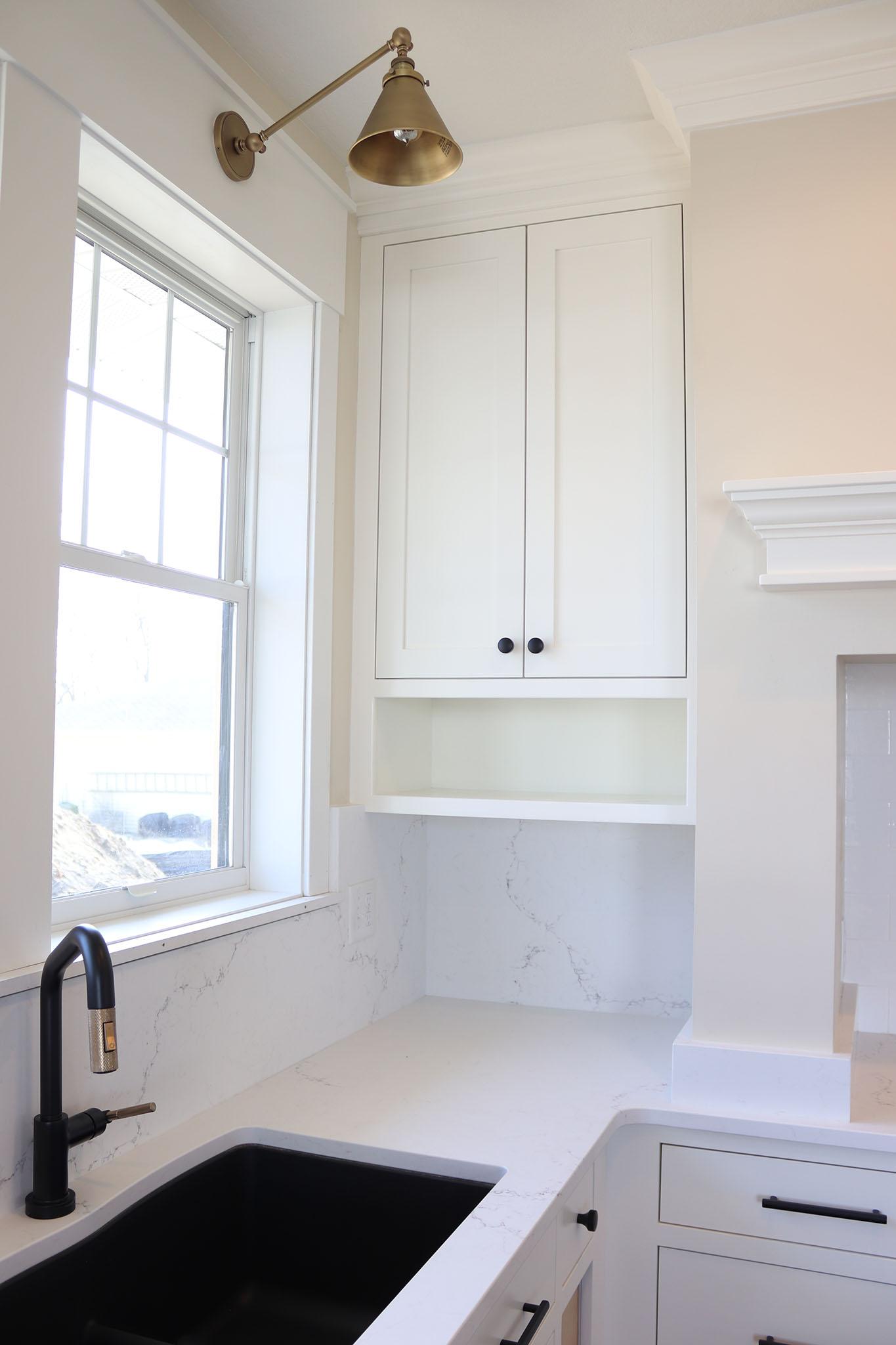 Black undermount kitchen sink with storage nook and cabinet