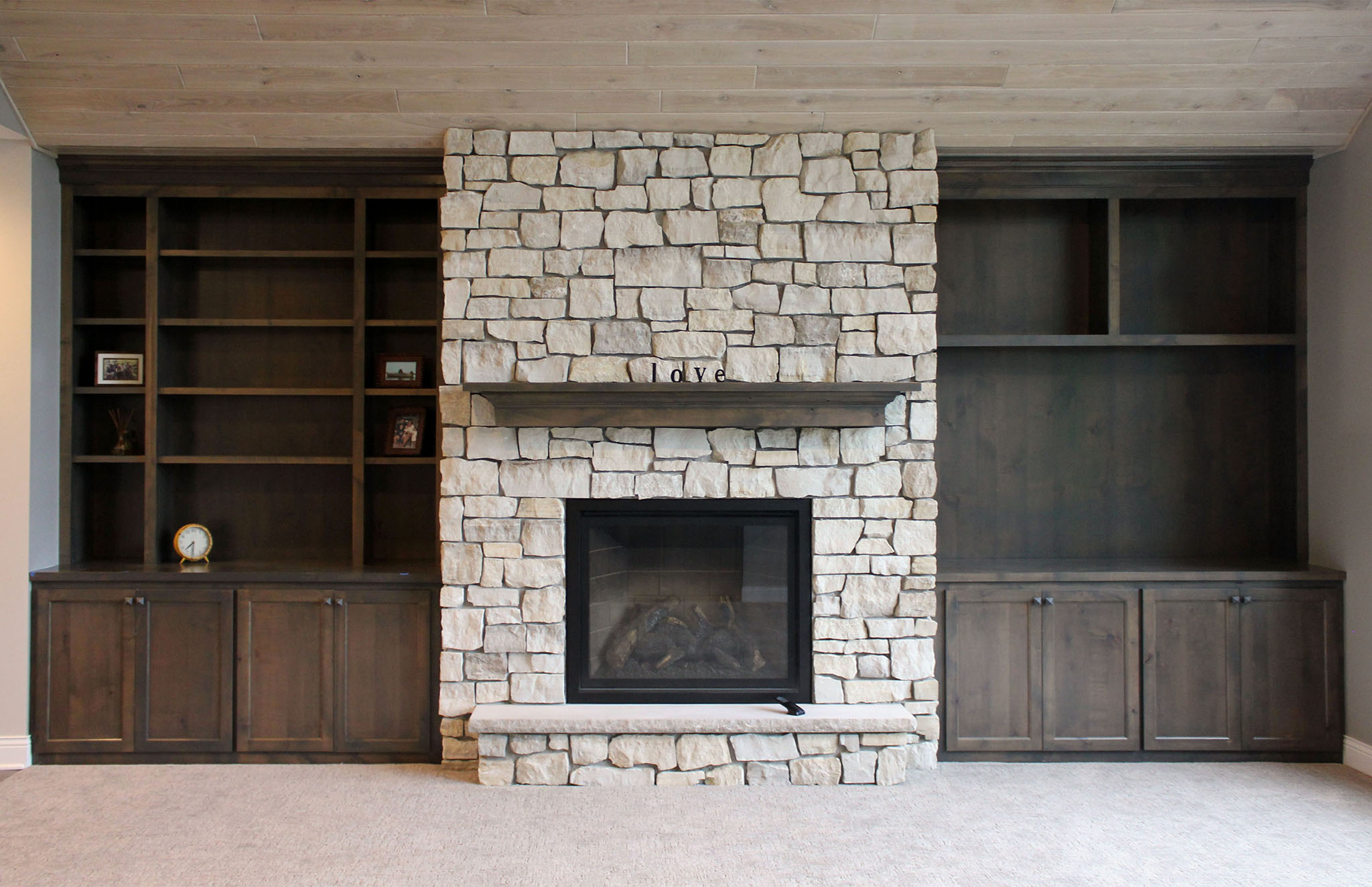 Traditional family room with stone fireplace, custom built-ins on each side and ash tongue and groove wood ceiling