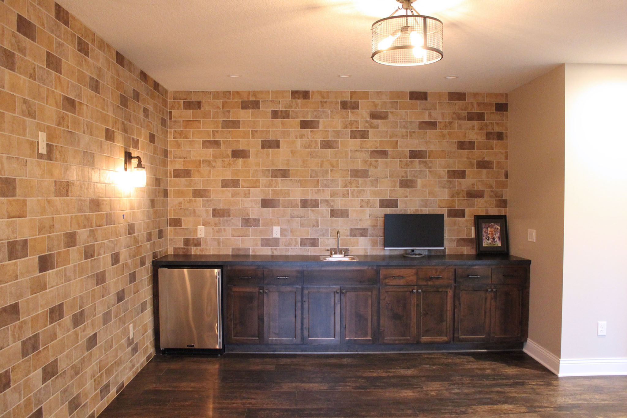 Rustic exposed brick wall with wet bar, undercounter cooler and base cabinet