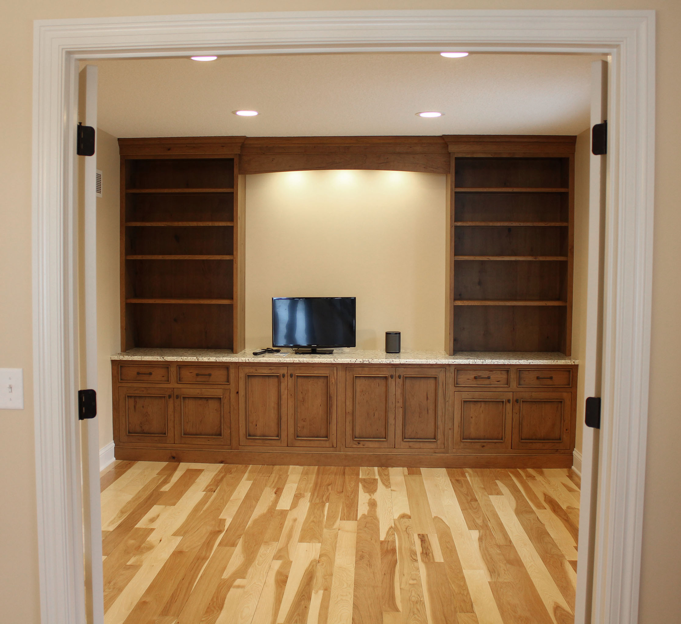 In-home office featuring custom wood cabinets with European hinges, inset doors, built-in shelves, granite countertop and varying sized wood floor planks