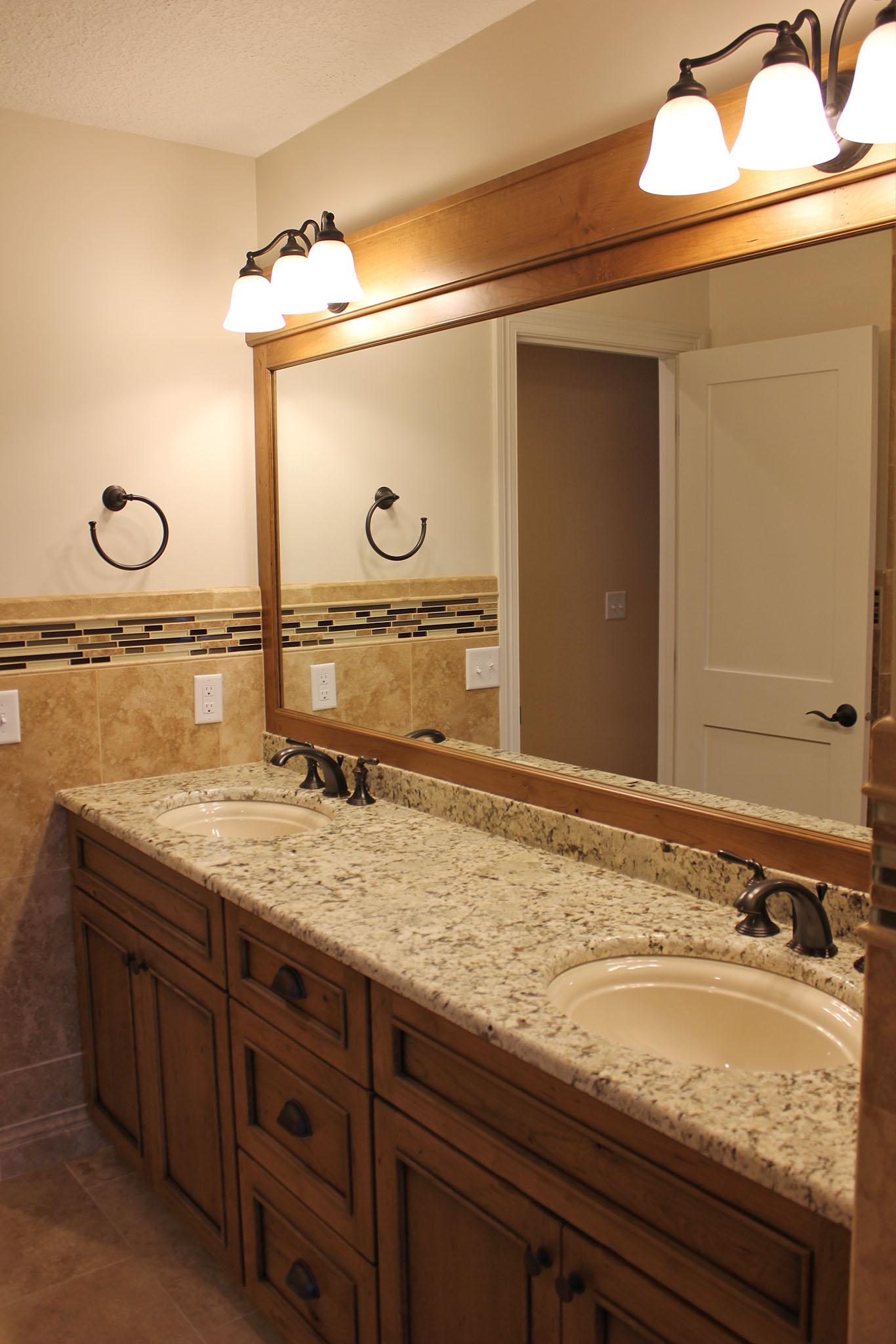 Master bath with custom cabinets, marble tops, undermount sink bowl, tile backsplash and wood framed mirror