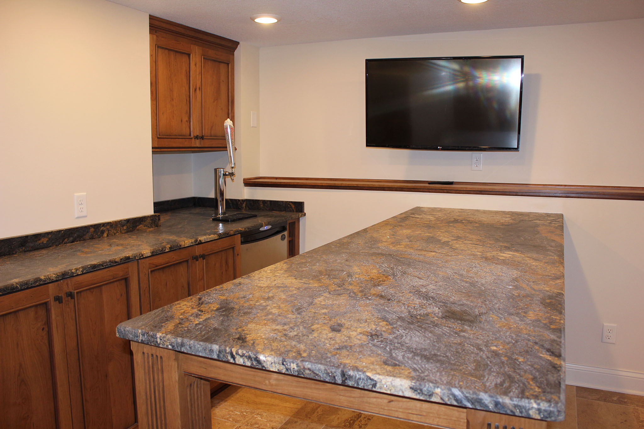 Basement man cave bar area with raised height cabinets, granite countertop, wall cabinets and a kegerator