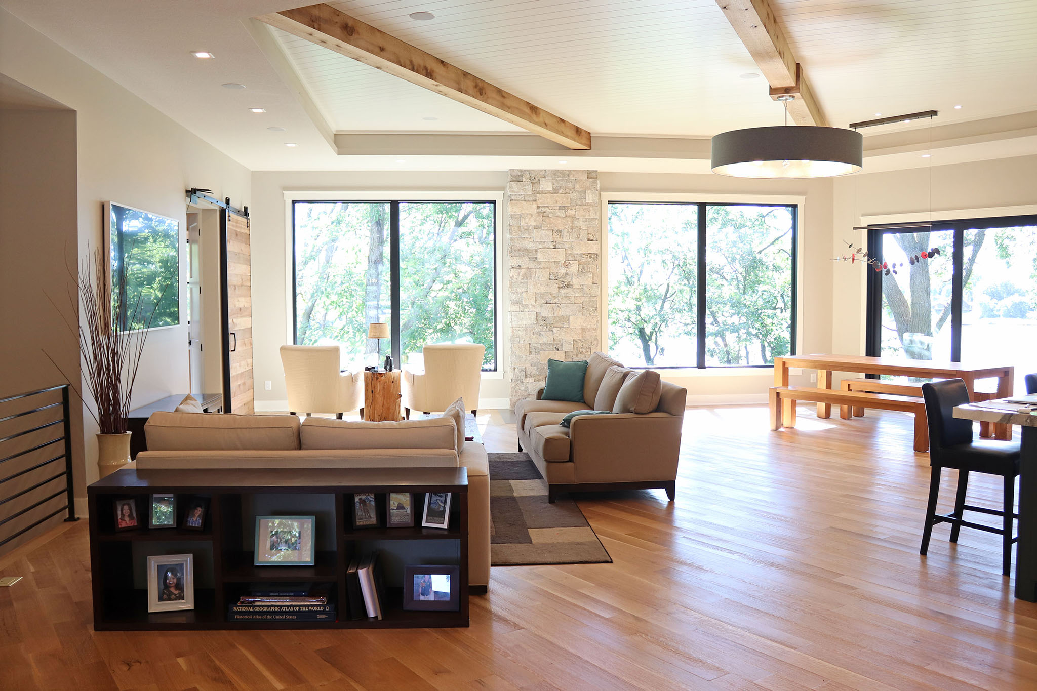 Contemporary great room and dining area with stone accent wall, tray ceiling with cedar wood beams