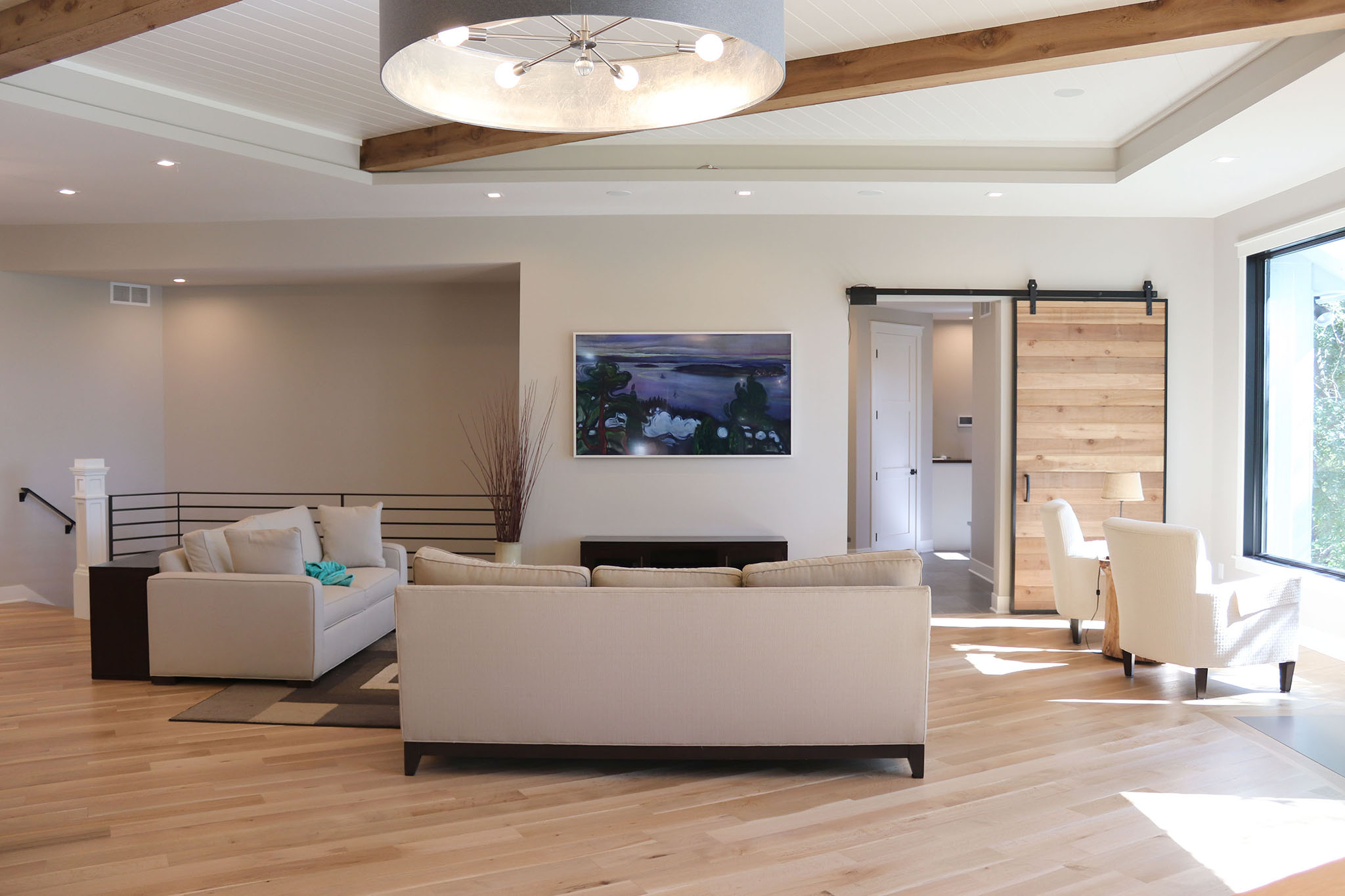 Contemporary great room with tray ceiling, cedar wood beams, sliding plank wood barn door and horizontal metal railing