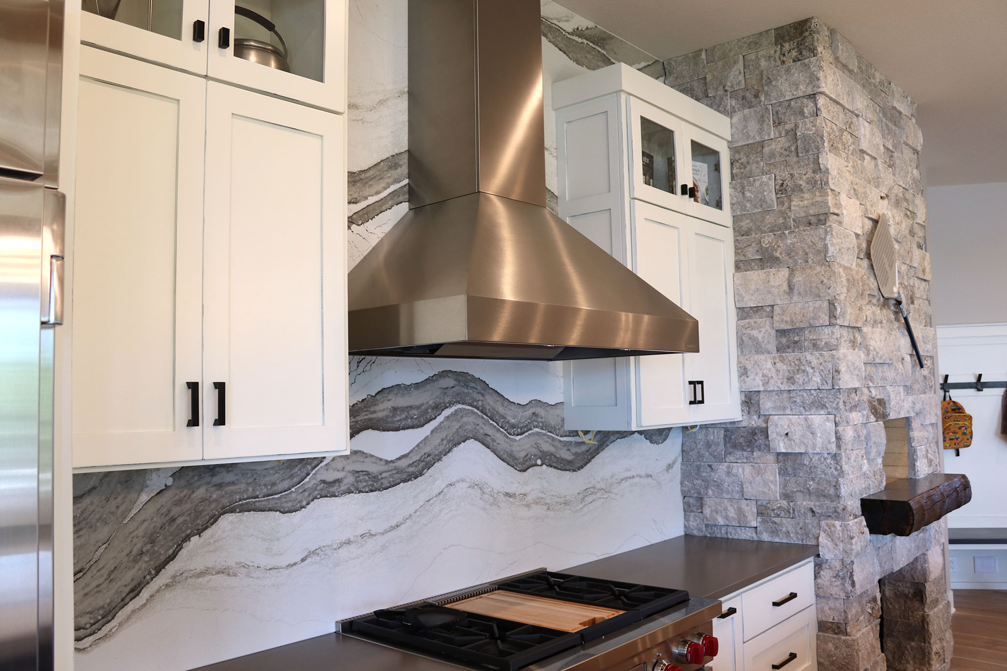 Digitally designed quartz vein in Cambria backsplash with stainless steel hood vent and indoor brick pizza oven