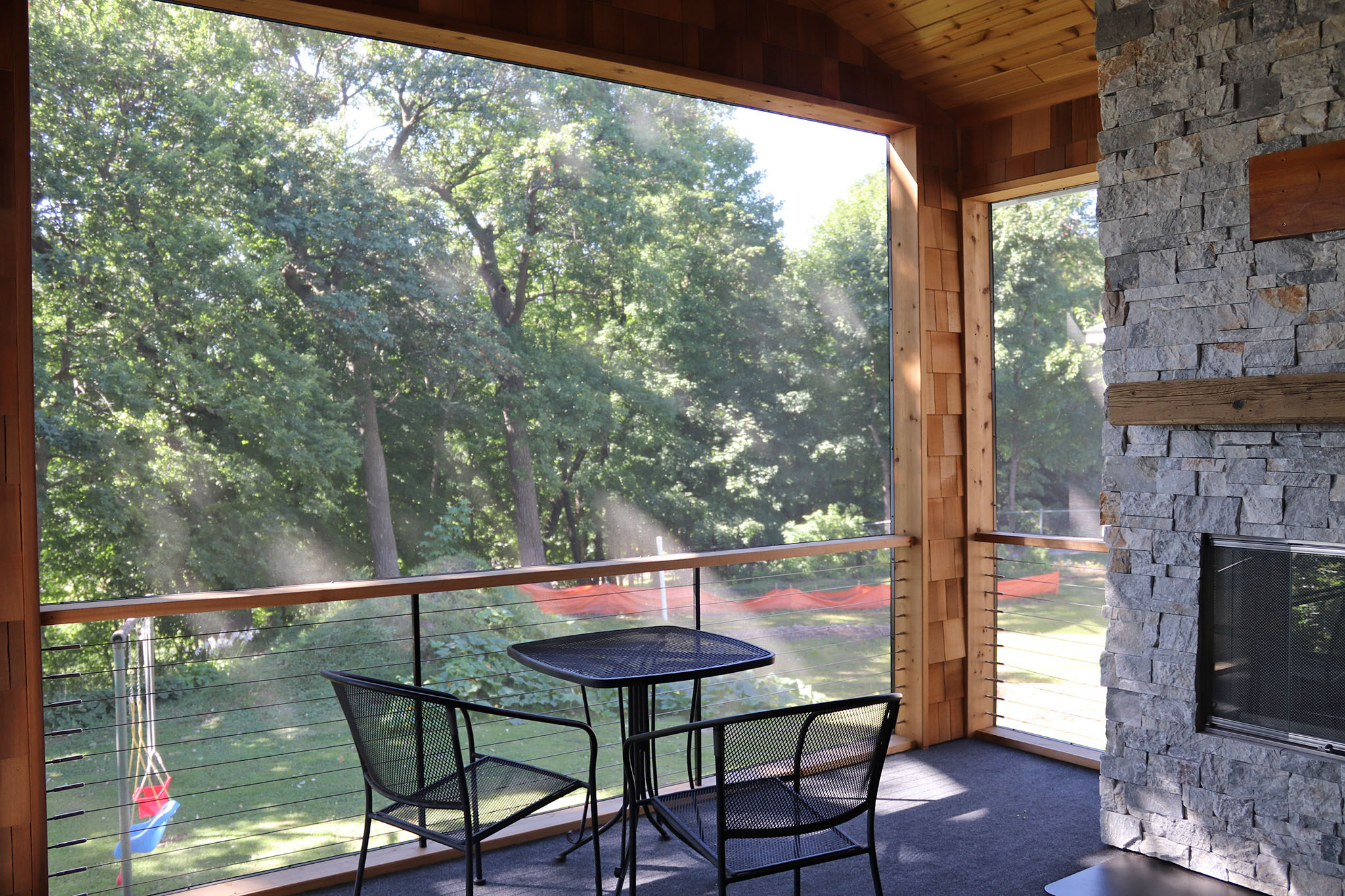 Screen porch with horizontal cable rail system, cedar lap siding, tongue and groove wood ceiling, stone fireplace