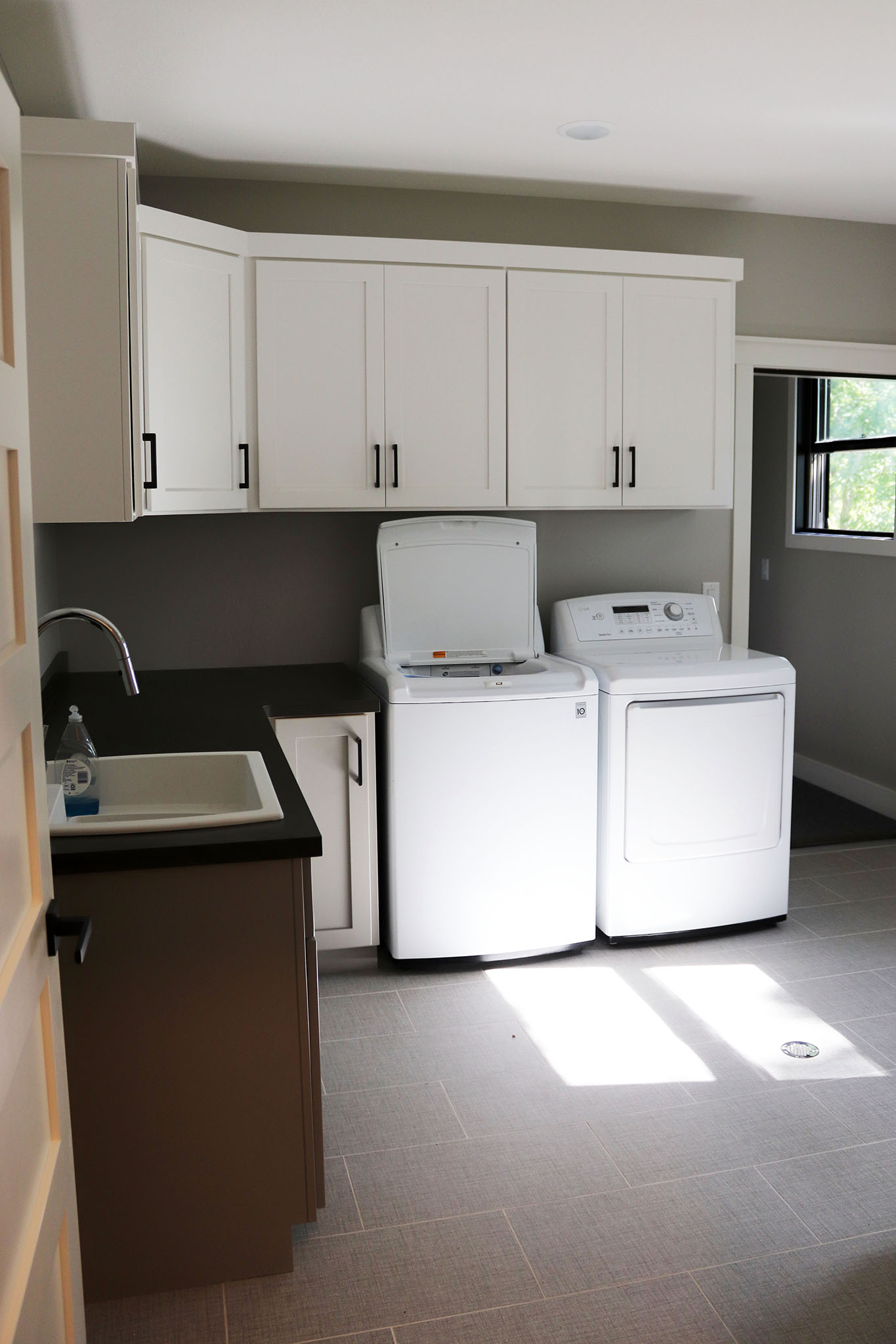 Spacious utility area with laundry, custom cabinets and built-in laundry tub sink