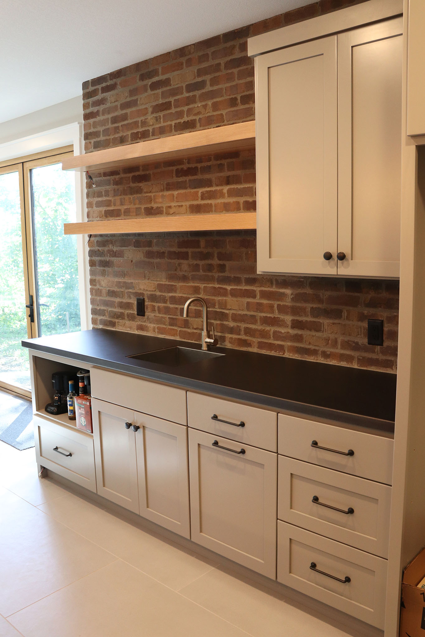 Basement wet bar with brick accent wall, painted custom cabinets, Cambria countertops and floating wood shelves