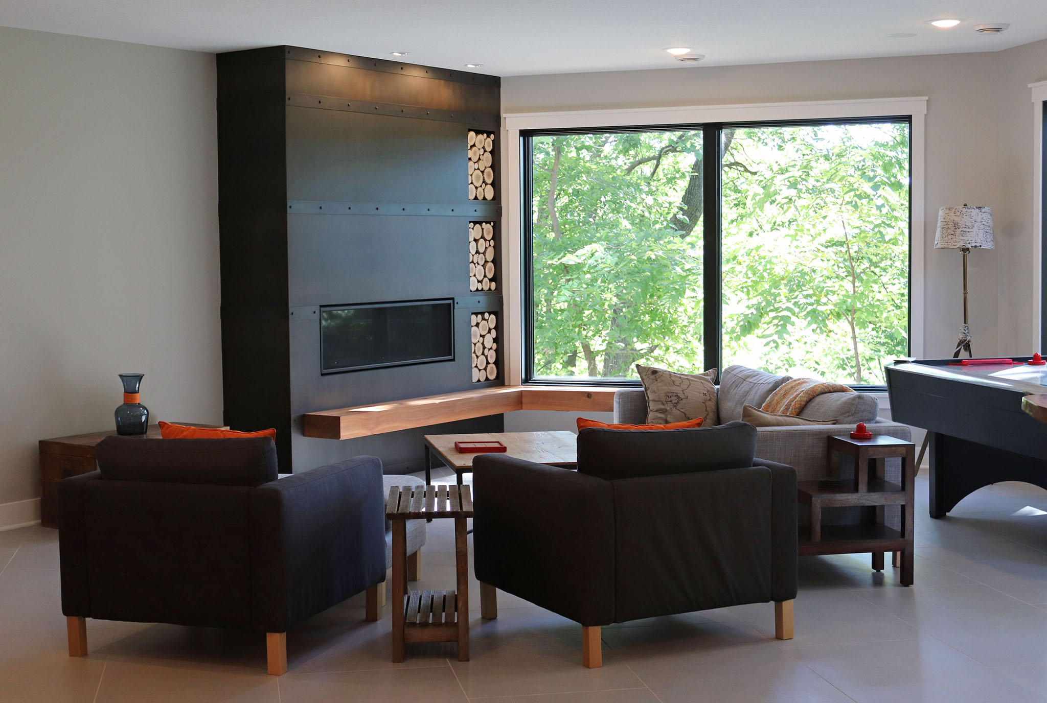 Open family room with contemporary fireplace, oversized Andersen black picture window, ceramic tile flooring and space for game tables