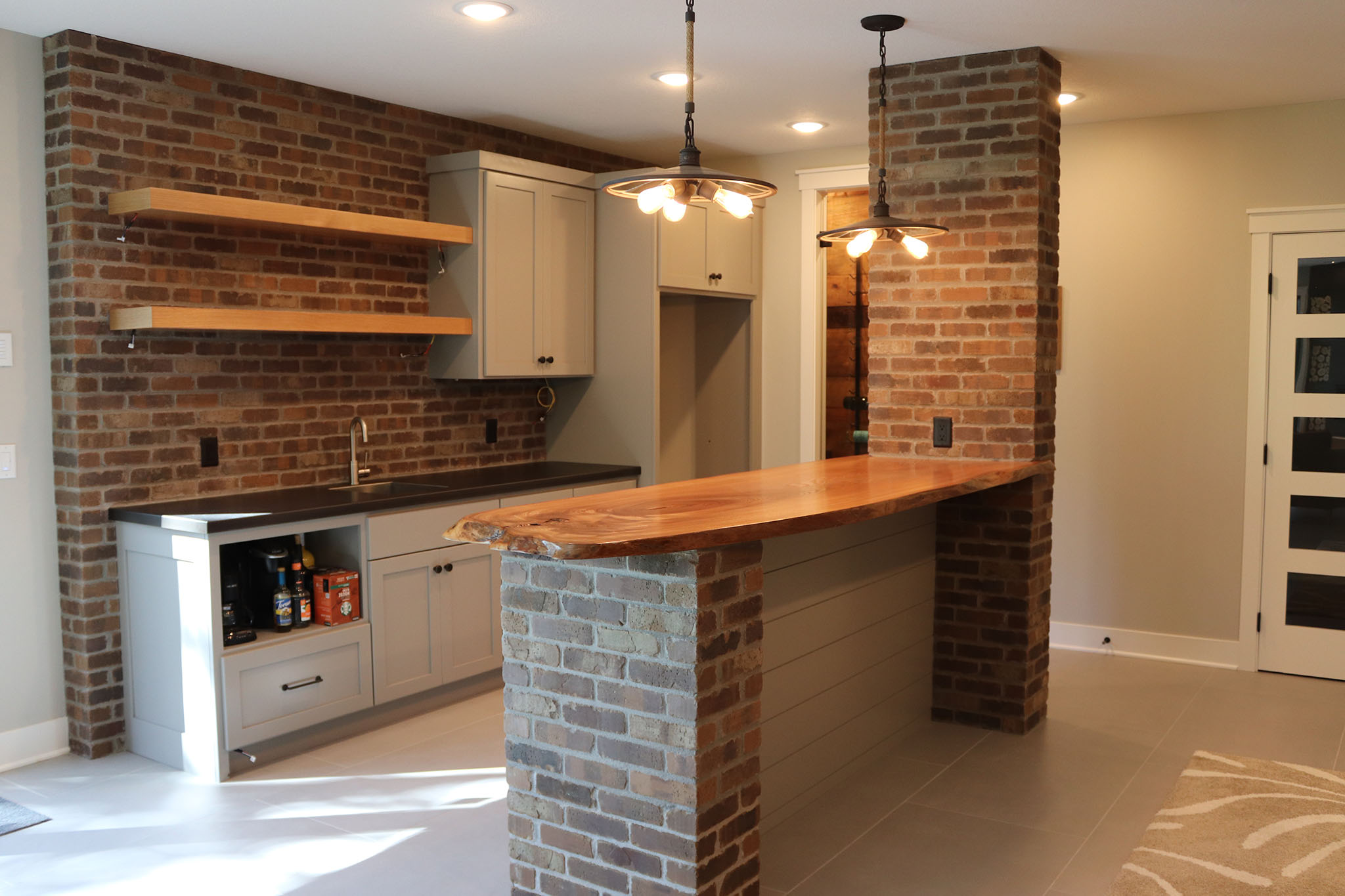 Basement bar area with brick accents, wood plank countertop, floating wood shelves, custom countertops and ceramic tile flooring