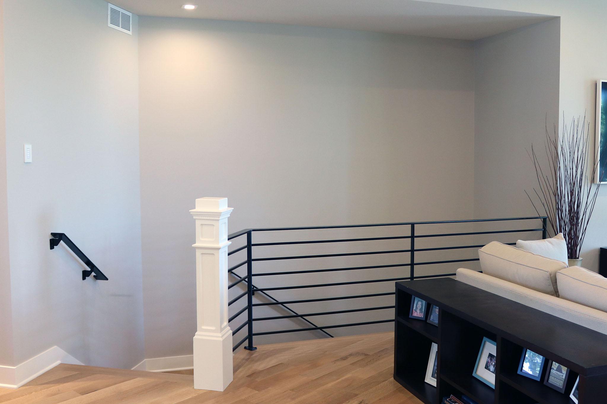 Modern horizontal black metal stair railing with bold painted wood newel post