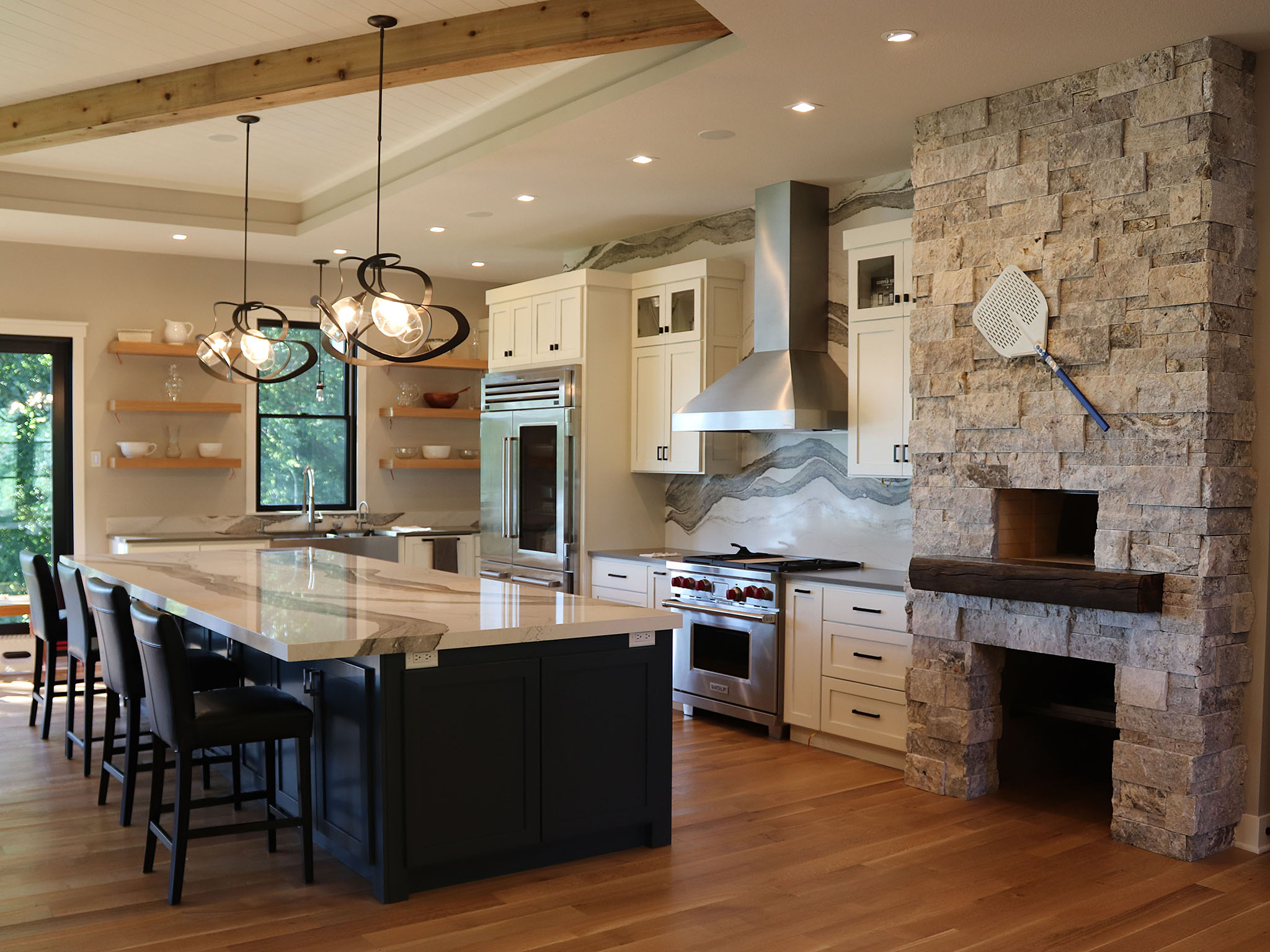 Spacious kitchen with digitally designed Cambria countertop and backsplash, brick oven, white cabinetry and floating shelves