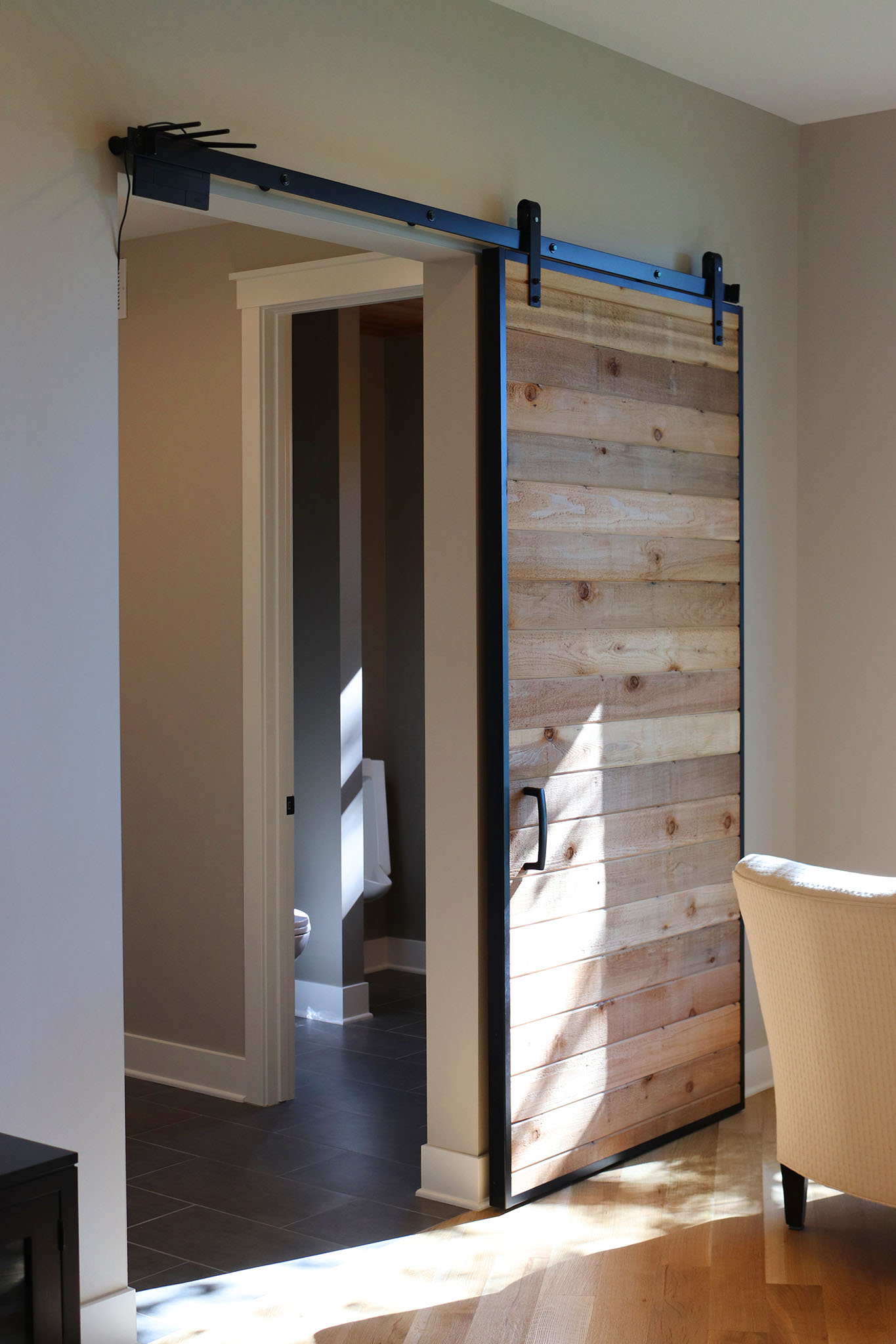 Barn door with rough wood plank and black satin hardware