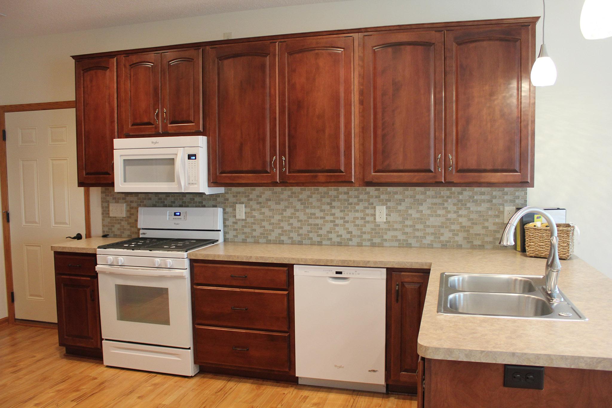Kitchen with tile backsplash and white appliances
