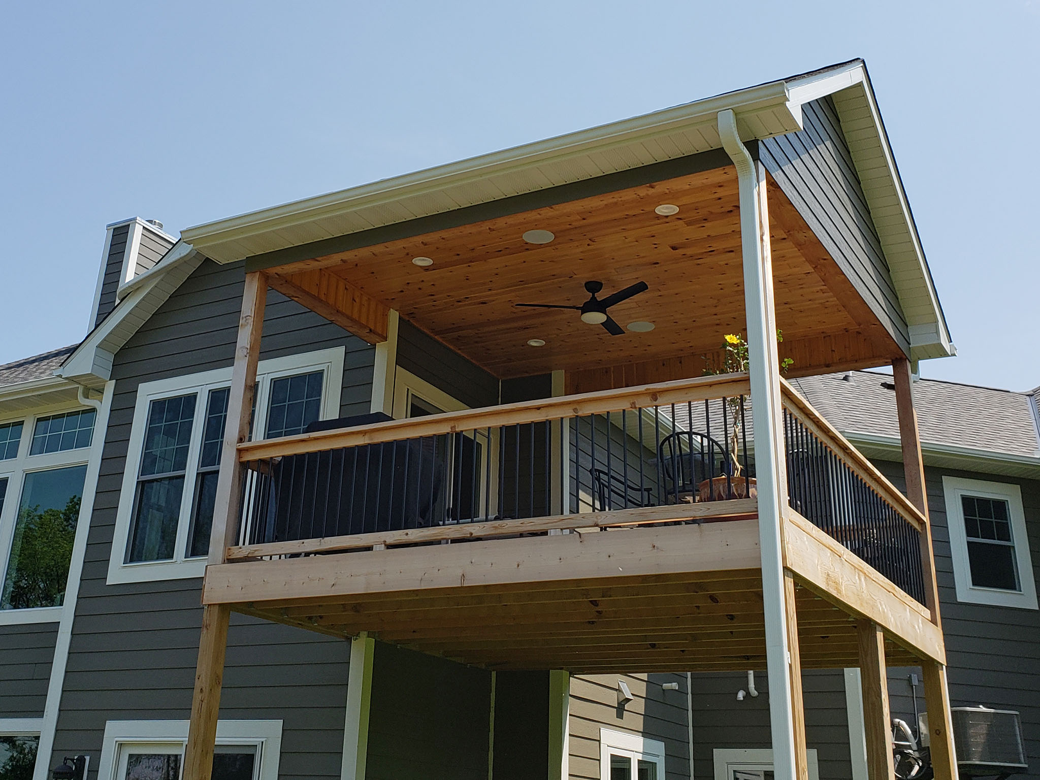 Cedar deck with metal balusters and wood railing, can lights and ceiling fan