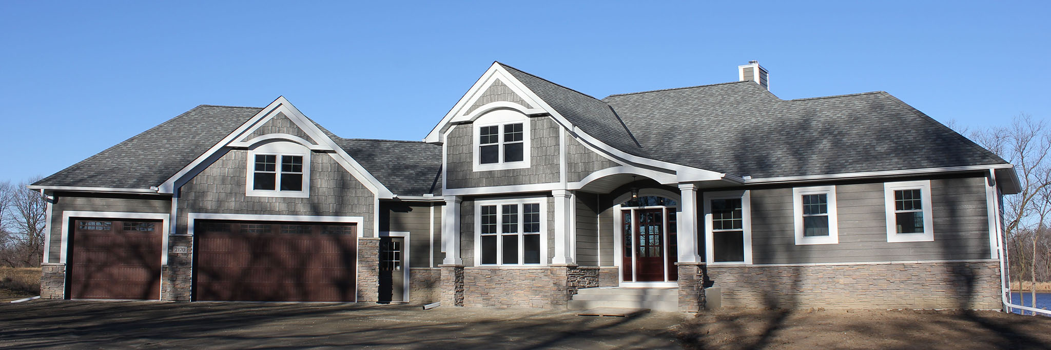 Sprawling rambler with three-stall garage, ledgestone wainscoat, LP Smartside and shakes and wide accent trim