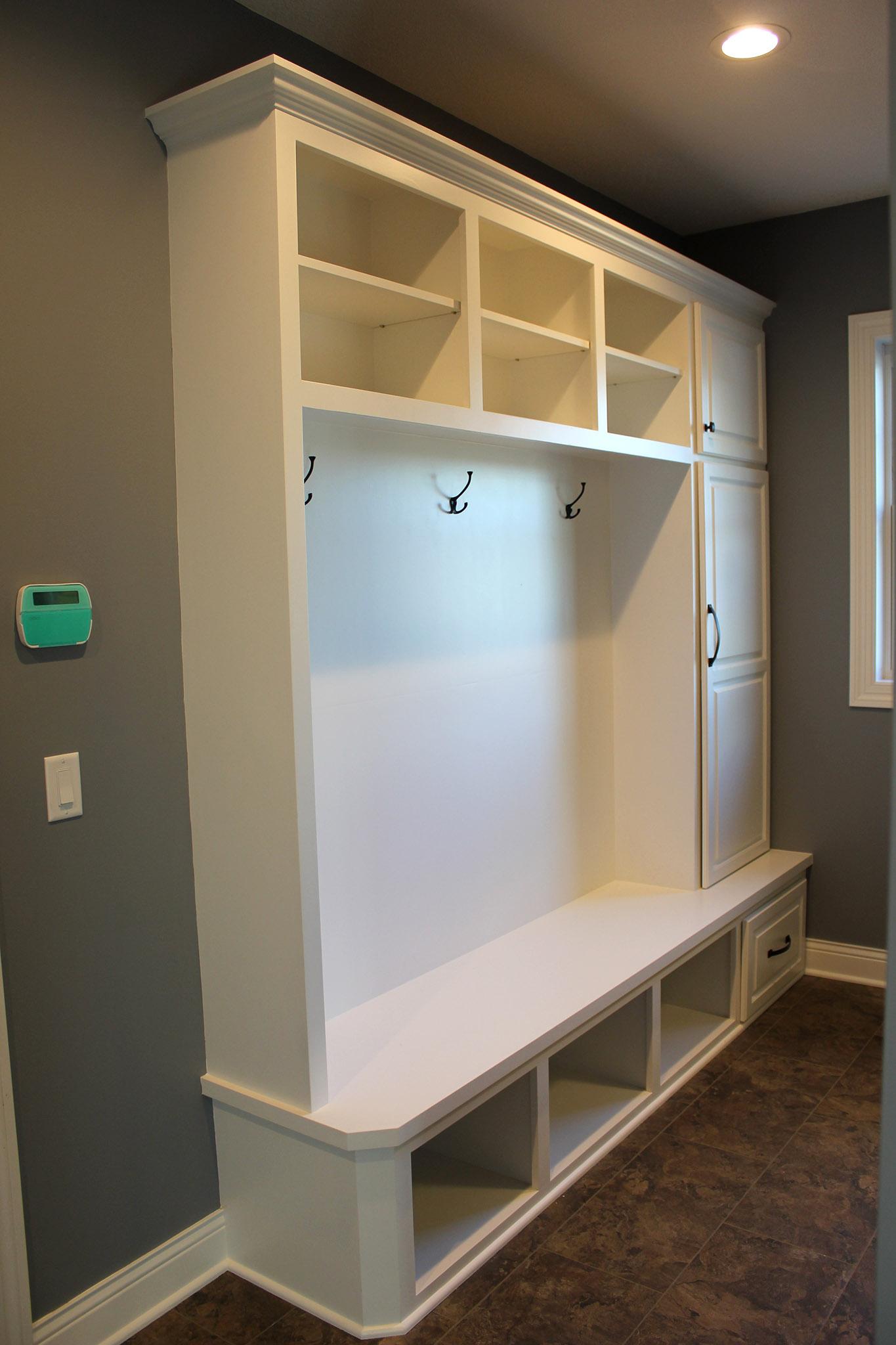 Mudroom storage lockers with coat hooks, open shoe storage below, open shelves above with ceramic tile flooring