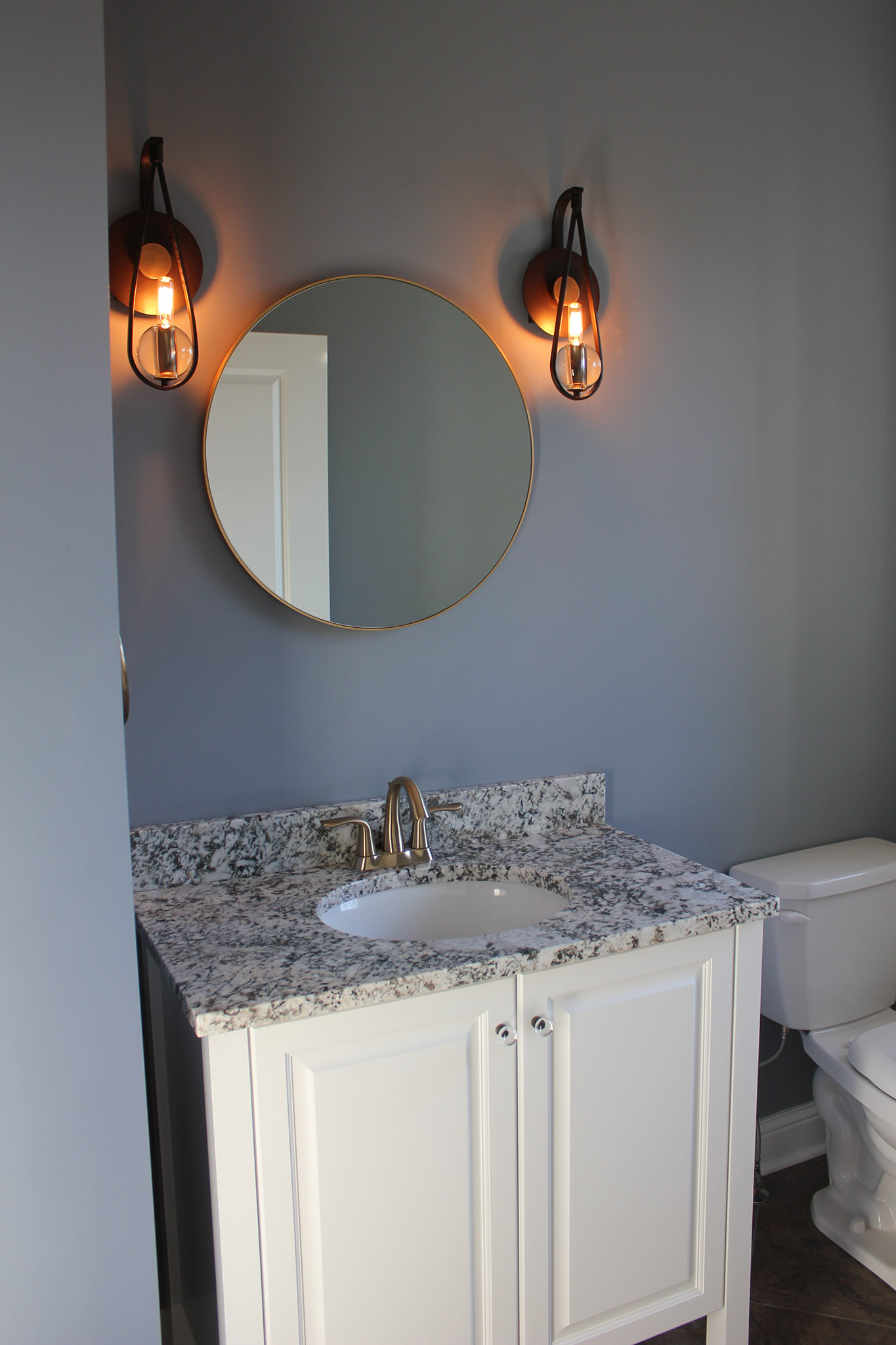 Free standing vanity with cultured marble top, ceramic undermount sink, round mirror and edison vanity lights