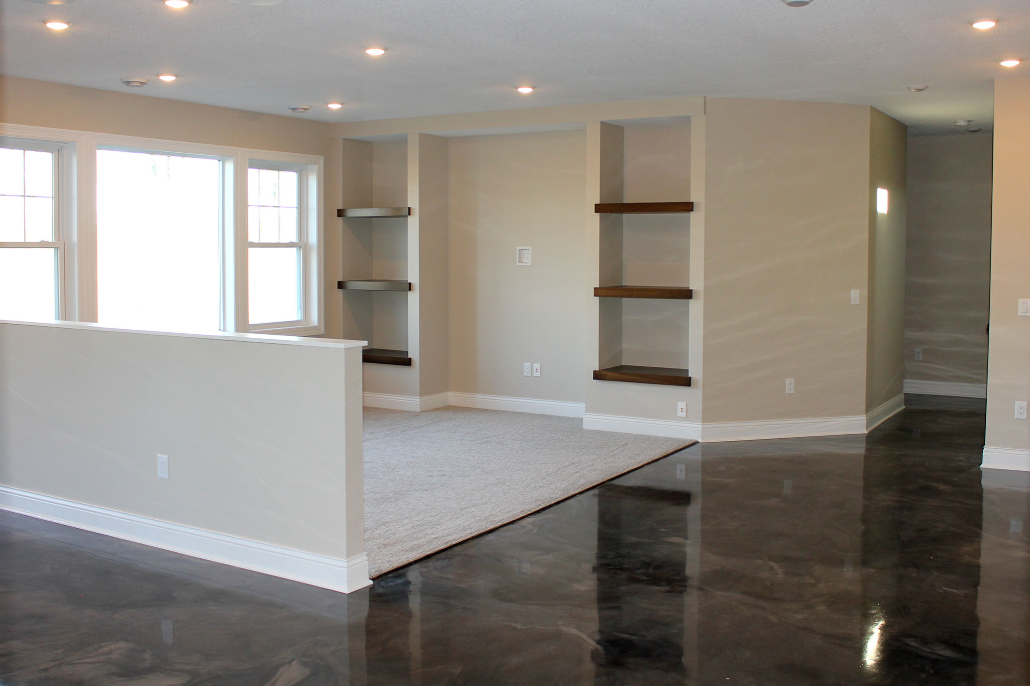 Basement family room with half wall divider, spot for TV/Entertainment console and floating wood shelves