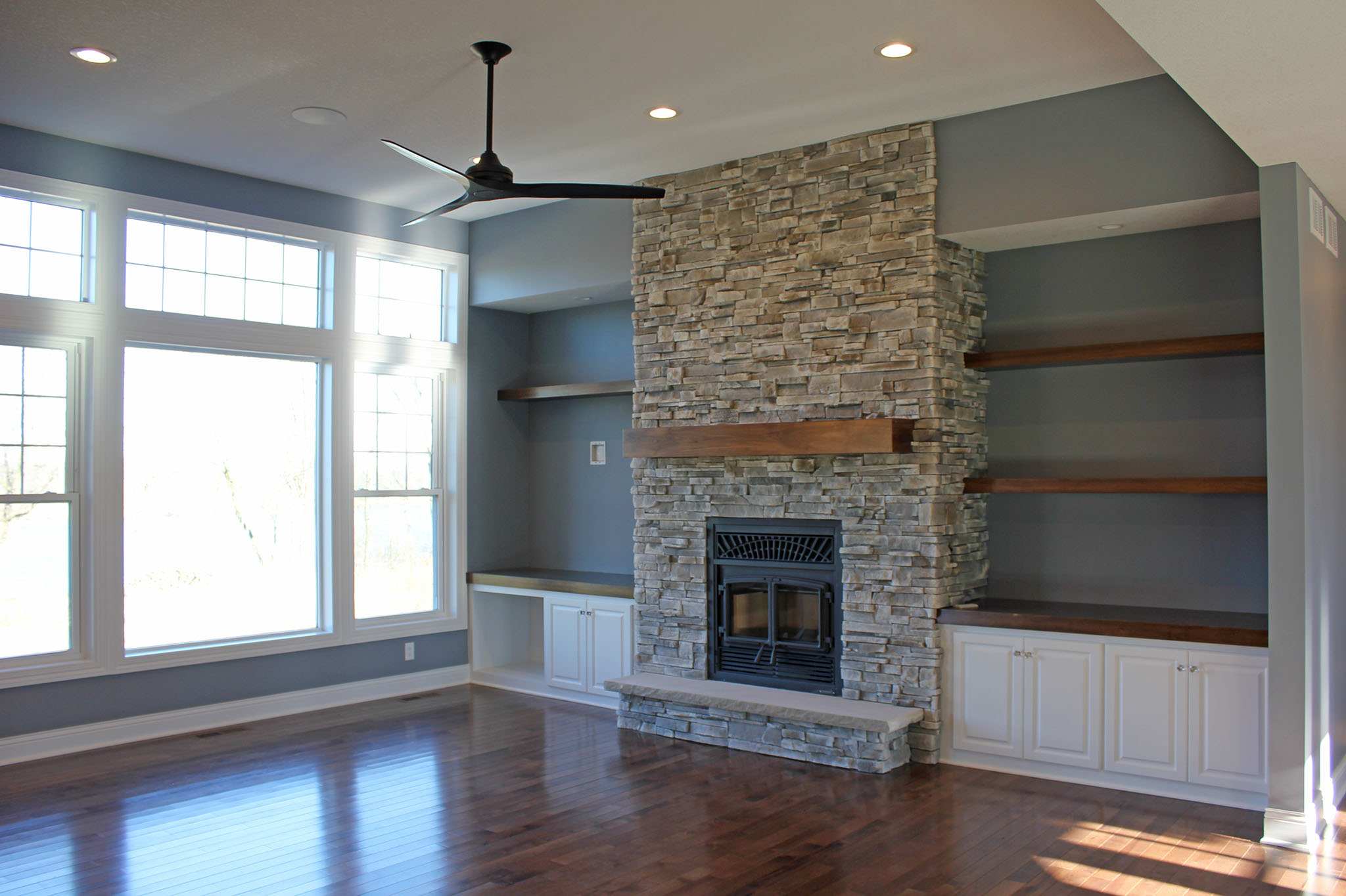 Great room with floor to ceiling wood burning stone fireplace, wood mantle, custom built-in cabinets, floating shelves