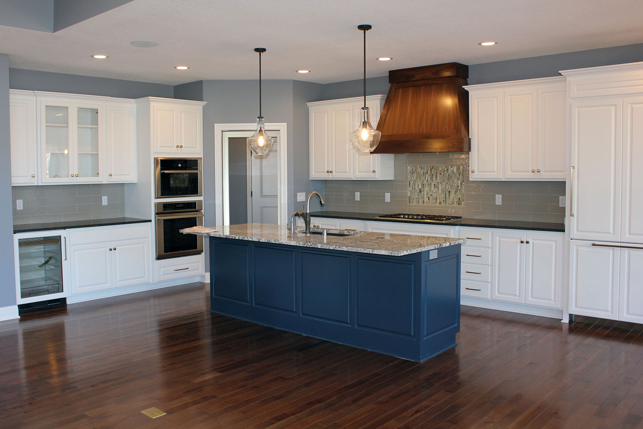 Fun white and blue two-toned kitchen with granite countertops, oven wall, wine cooler, and set-in mosaic glass backsplash