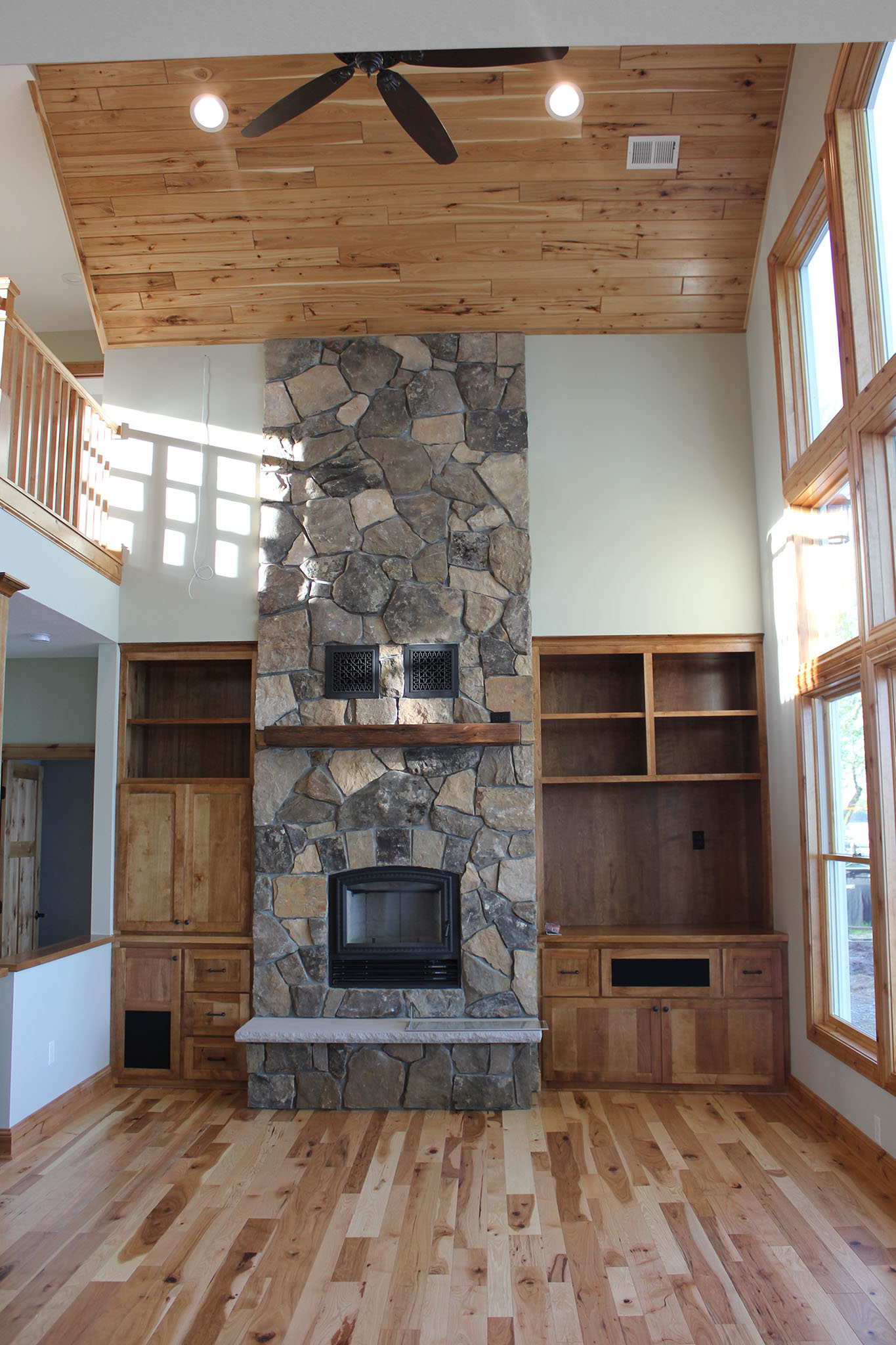 Great room with massive stone wood burning fireplace, built-in cabinets, hickory wood flooring and tongue and groove wood ceiling