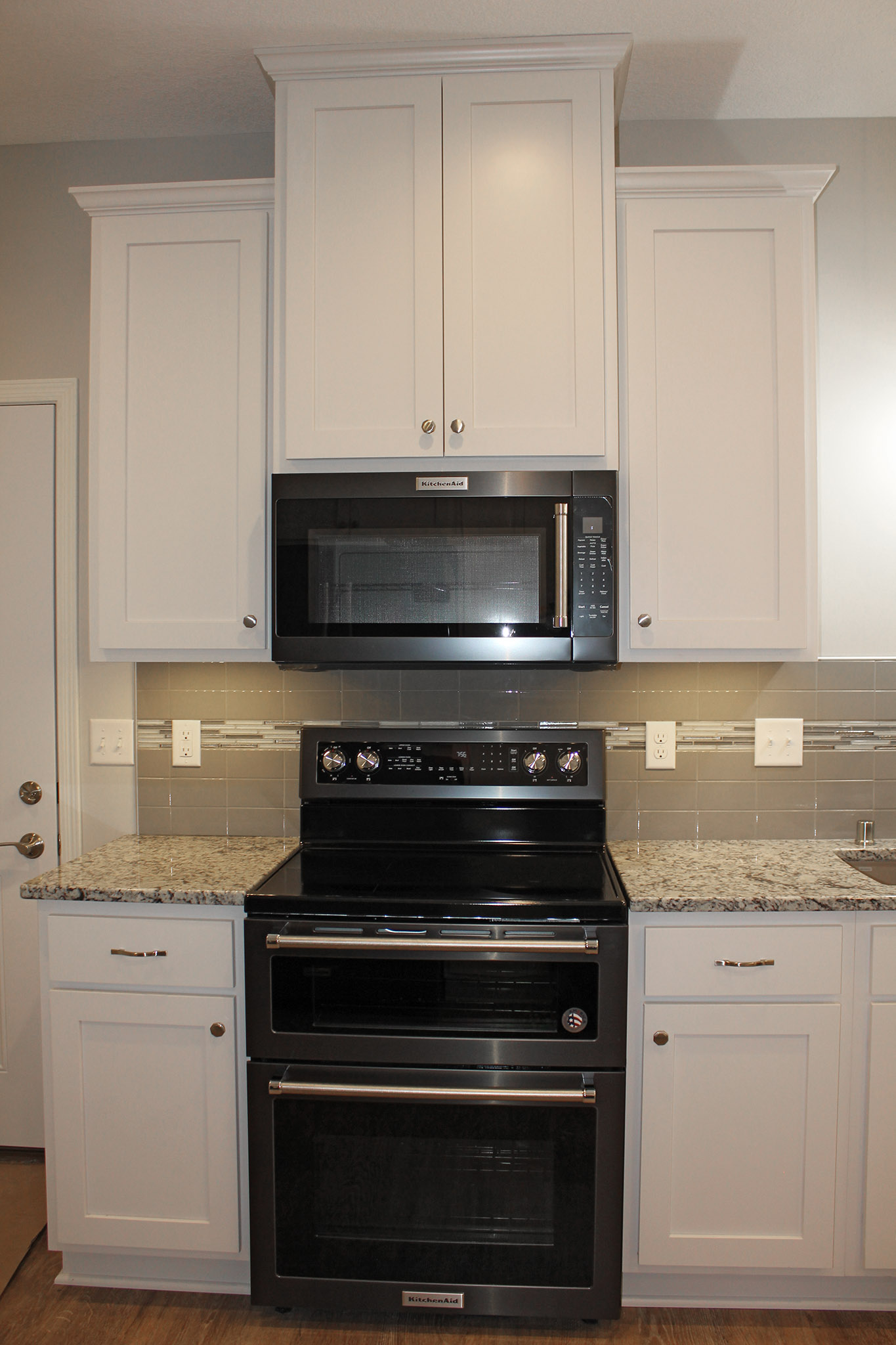 Black stainless appliances with white cabinets